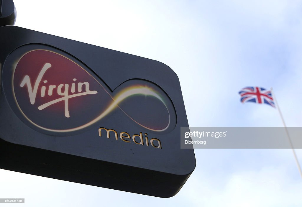 The Virgin Media company sign sits outside their store on Oxford Street opposite a Union Jack flag in London, U.K., on Wednesday, Feb. 6, 2013. Billionaire John Malone's Liberty Global Inc. agreed to acquire Virgin Media, Britain's second-largest pay-TV provider, in a $16 billion cash-and-stock transaction announced in the U.S. yesterday. Photographer: Chris Ratcliffe/Bloomberg via Getty Images