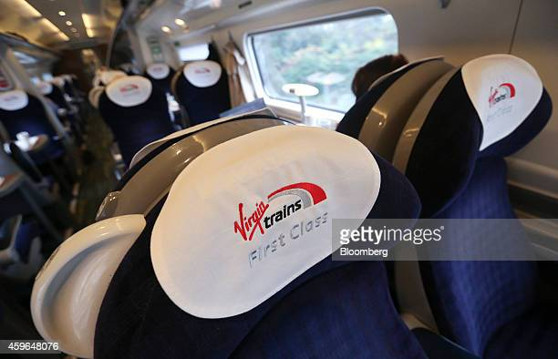 The Virgin Trains logo sits on first class carriage seat antimacassars on board a West Coast train as it travels from London to Milton Keynes UK on...