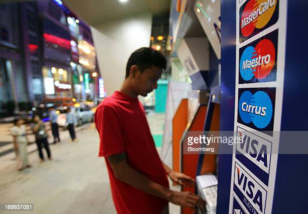 The Visa Inc and Mastercard Inc logos are displayed on the side of an automated teller machine as a customer withdraws money at a shopping mall in...