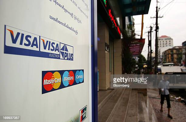 The Visa Inc and Mastercard Inc logos are displayed on the side of an automated teller machine outside a supermarket in downtown Yangon Myanmar on...