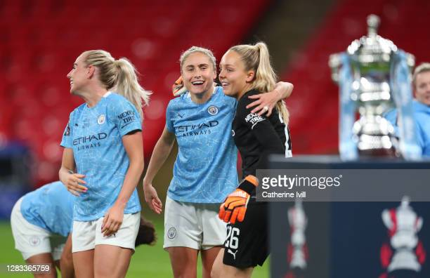 The Vitality Women's FA Cup Trophy is seen as Steph Houghton of Manchester City and Ellie Roebuck of Manchester City celebrate following their team's...