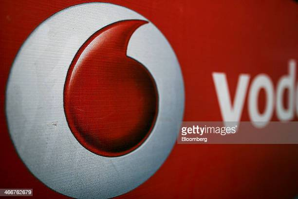 The Vodafone Group Plc logo is displayed outside a mobile phone store in Mumbai India on Wednesday Jan 29 2014 India got bids totaling 4461 billion...