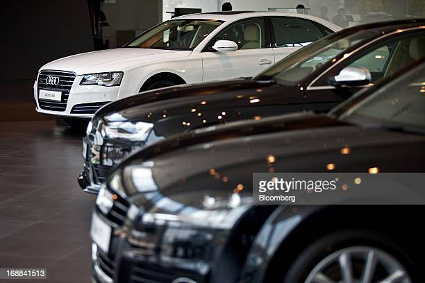 The Volkswagen AG Audi A8L left Audi A4 center and Audi TT vehicles stand on display inside the Audi Delhi South dealership in New Delhi India on...