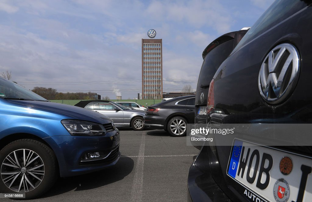 The Volkswagen AG (VW) headquarters stand beyond automobiles in an employee parking lot in Wolfsburg, Germany, on Friday, April 13, 2018. Volkswagen AGs new top manager pledged to speed up the German carmaking giants decision-making as it confronts a seismic industry change in technology while moving beyond its diesel-emissions scandal. Photographer: Krisztian Bocsi/Bloomberg via Getty Images
