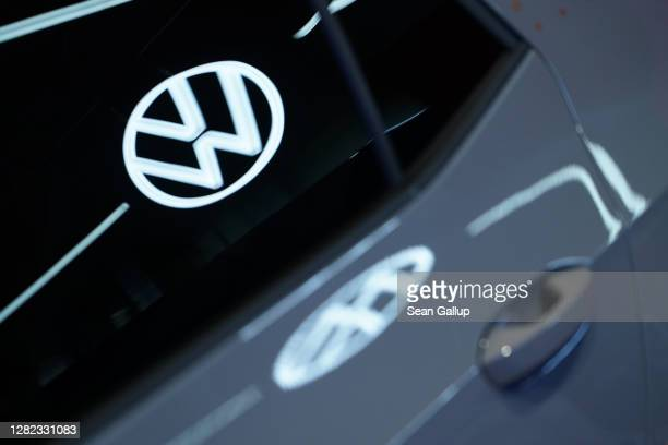 The Volkswagen logo is reflected in the window and body of a Volkswagen ID.3 electric car standingt on display at the Autostadt promotional facility...