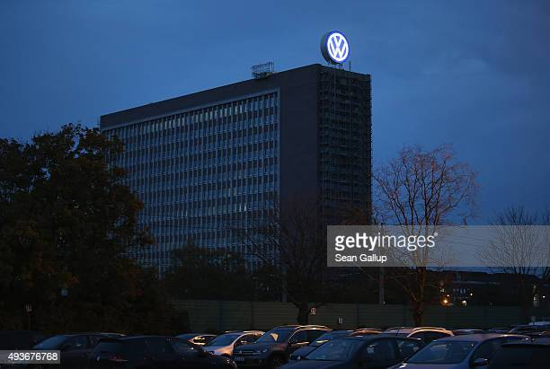 The Volkswagen logo stands illuminated on an administrative building at the Volkswagen factory and company headquarters near an employee parking lot...