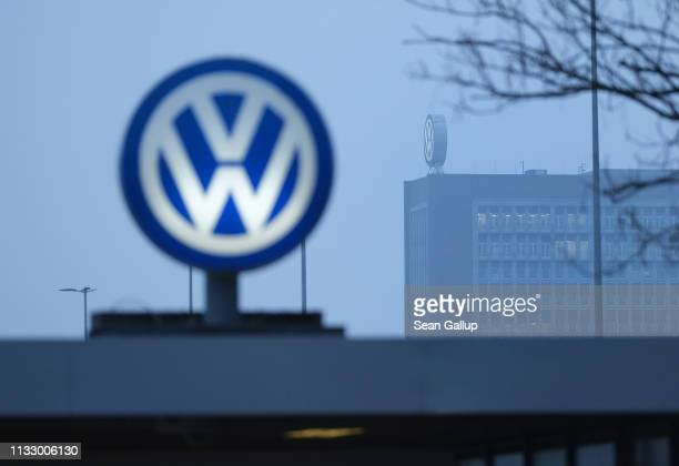 The Volkswagen logo stands over an entrance gate as the main Volkswagen corporate office building stands behind at the Volkswagen factory on March...