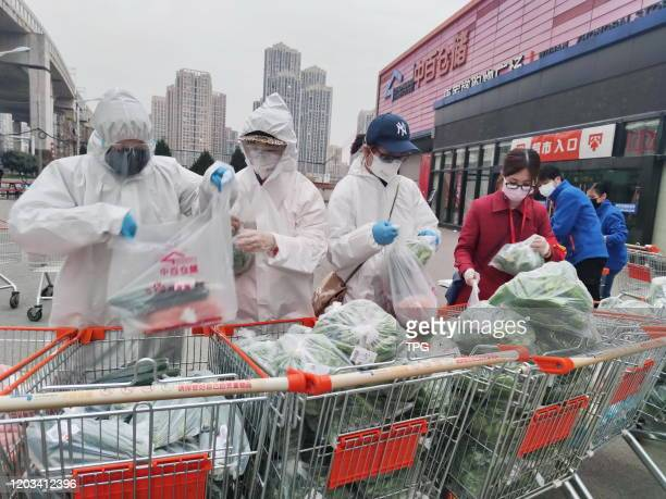 The volunteers and community staff are preparing fresh vegetables for citizens in the sealed city during the outbreaks of novel coronavirus pneumonia...