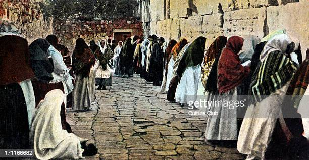 The Wailing Wall in the old city of Jerusalem with women praying Wearing shawls over their heads Men praying on the far side of the photo