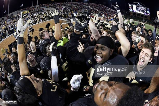 The Wake Forest Demon Deacons celebrate an upset victory over the North Carolina State Wolfpack following the football game at BBT Field on November...