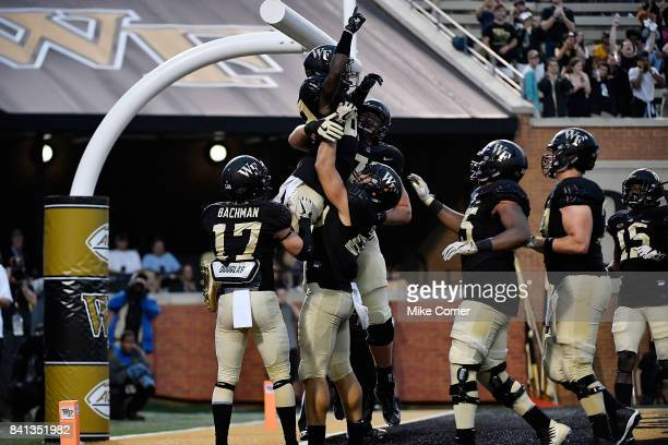The Wake Forest Demon Deacons lift wide receiver Greg Dortch after he makes a touchdown reception against the Presbyterian Blue Hose at BBT Field on...