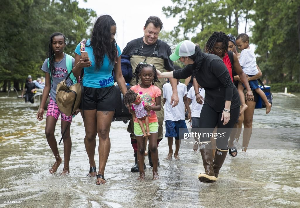 The Walker and Brown families walk out of the water at Memorial Drive and North Eldridge Parkway in the Energy Corridor of west Houston, Texas where residents rescued from their flooded homes and apartments due to high water coming from the Addicks Reservoir after Hurricane Harvey. Harvey, which made landfall north of Corpus Christi August 25, has dumped more than 50 inches of rain in some areas in and around Houston.