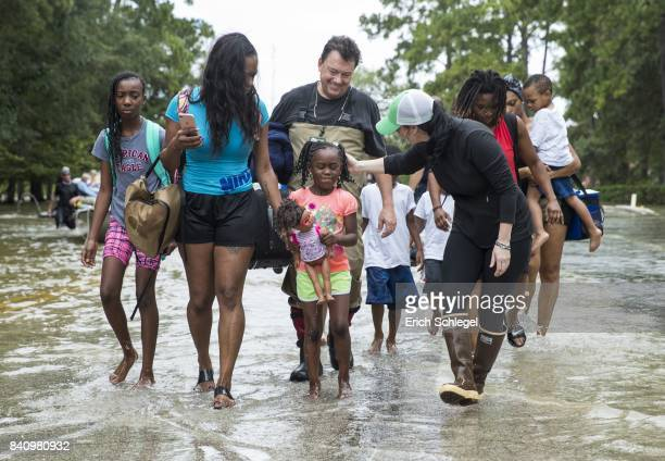 The Walker and Brown families walk out of the water at Memorial Drive and North Eldridge Parkway in the Energy Corridor of west Houston Texas where...