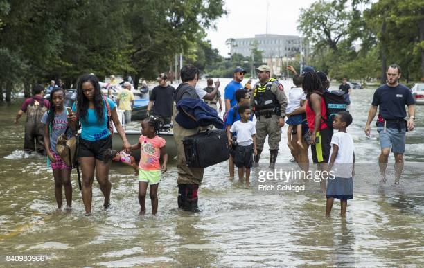 The Walker and Brown families walk out of the water at Memorial Drive and North Eldridge Parkway in the Energy Corridor of west Houston where...