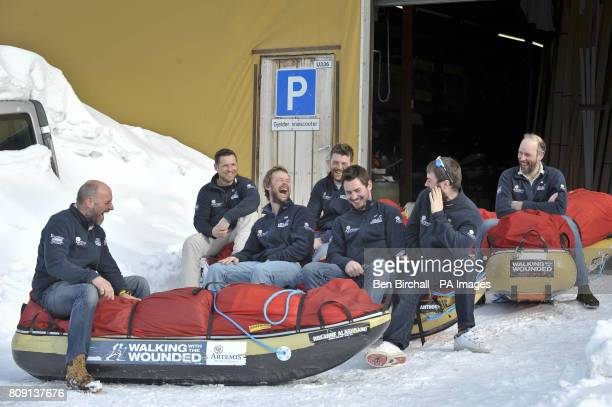 The walking with the wounded team relax and share a joke sat on their pulks as they arrive back in Longyearbyen Svalbard in the Arctic Circle after...