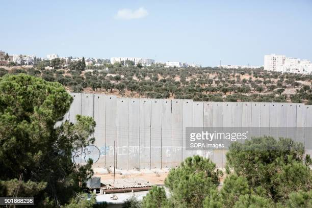 The wall that separates the West Bank and Israel and the approaching Israeli settlement buildings Bethlehem is a town located in the west bank area...