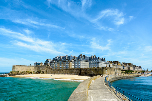 The walled city of Saint-Malo, France, with granite residential buildings protruding above the rampart and the Mole beach at the foot of the fortifications, seen from the breakwater. 999432182