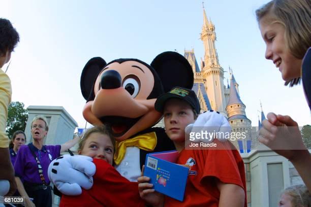 The Walt Disney character Mickey Mouse greets children at Magic Kingdom November 11 2001 in Orlando Florida