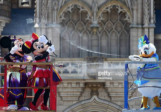The Walt Disney Co characters Mickey Mouse from left Minnie Mouse and Daisy Duck spray water as they perform in front of the Cinderella Castle during...
