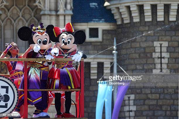 The Walt Disney Co characters Mickey Mouse front left and Minnie Mouse perform in front of the Cinderella Castle during an event named 'Disney Natsu...