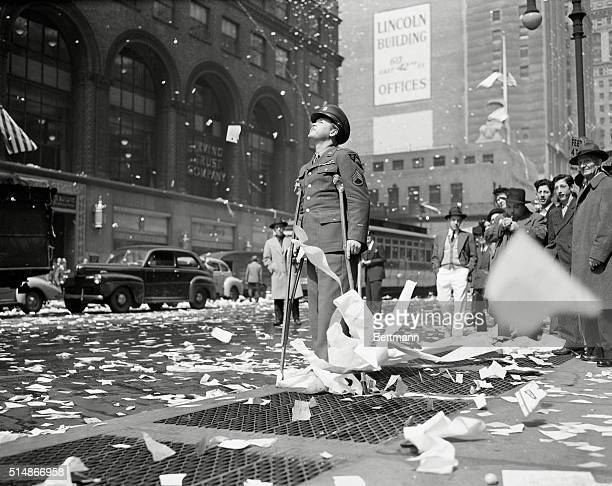The war in Europe is over Wounded veteran Arthur Moore looks up as he watches the tickertape rain down from buildings