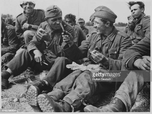 The War Is Over For Them Grinning broadly captured German soldiers on the beach of France find that the US Army 'K' rations are not as bad as the...