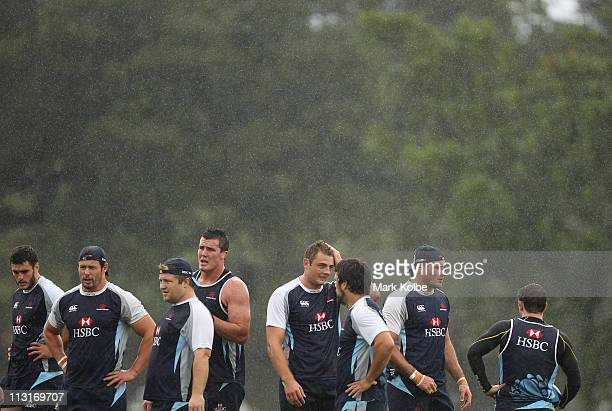 The Waratahs players stand in the rain during a Waratahs Super Rugby training session at Moore Park on April 26 2011 in Sydney Australia