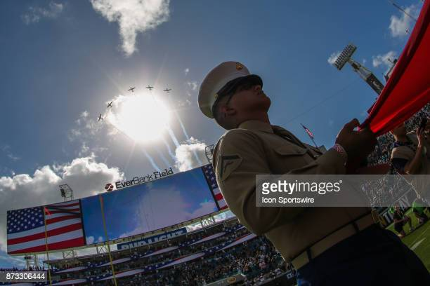 The Warbirds Flyover Team performs a flyover following the National Anthem as a serviceman holds the US Flag during pregame festivities in the Salute...
