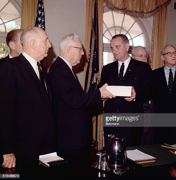 The Warren Commission hands to President Johnson at the White House today its voluminous report on the Kennedy assassination Left to right John J...