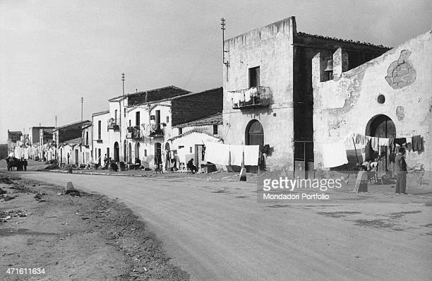 'The washing hanged out for drying in front of the houses in a street of the city Agrigento December 1956 '