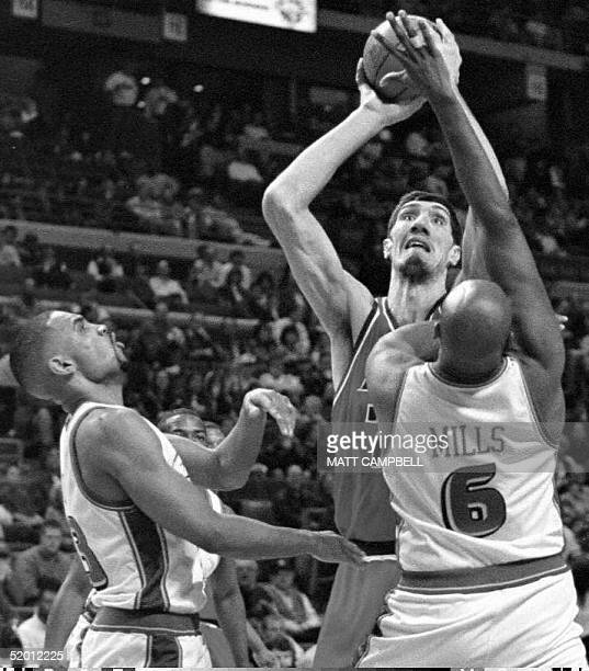 The Washington Bullets' Gheorghe Muresan puts a shot up over the Detroit Pistons' Terry Mills and Grant Hill in the first quarter 19 February at the...