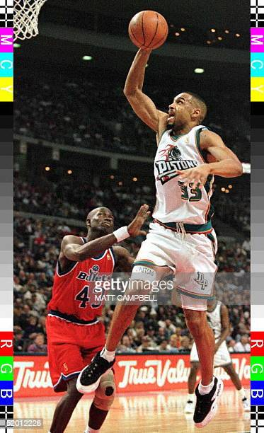 The Washington Bullets' Lorenzo Williams watches as the Detroit Pistons' Grant Hill drives past him for a dunk in the third quarter 19 February at...