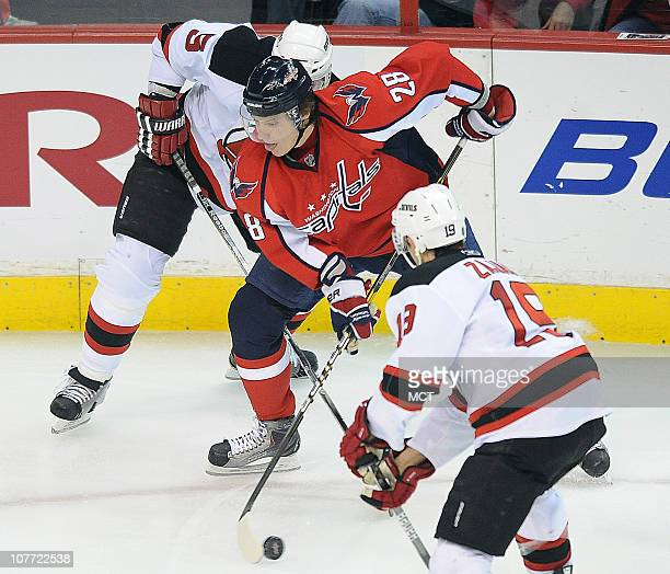 The Washington Capitals' Alexander Semin works the puck between New Jersey Devils defenseman Colin White and Devils center Travis Zajac during...