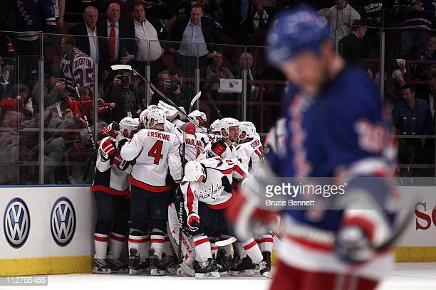The Washington Capitals celebrate their 43 double overtime win as Bryan McCabe of the New York Rangers skates dejected in the foregroun in Game Four...