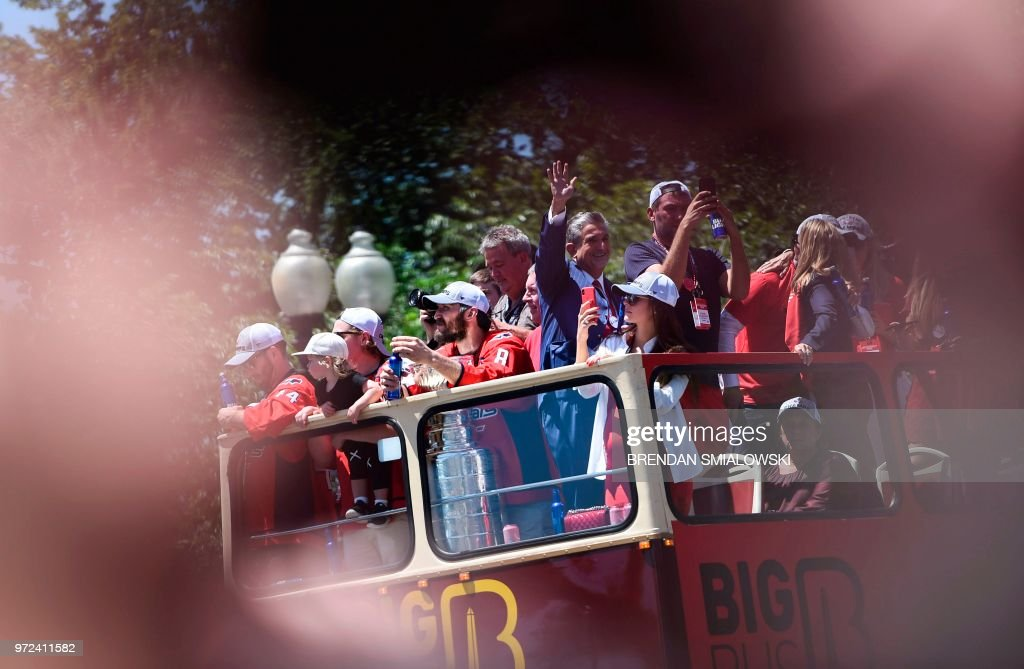 The Washington Capitals ride a bus with the Stanley Cup during their NHL hockey victory parade on June 12, 2018, in Washington,DC.