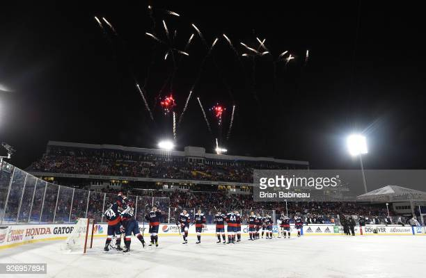 The Washington Capitals skate over to and congratulate goaltender Braden Holtby after their 5-2 win against the Toronto Maple Leafs while fireworks...