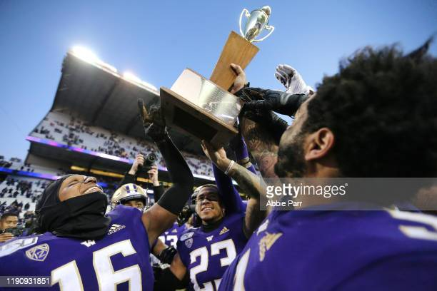 The Washington Huskies celebrate with the Apple Cup trophy after defeating the Washington State Cougars 31-13 during their game at Husky Stadium on...