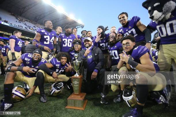 The Washington Huskies pose with the Apple Cup trophy after defeating the Washington State Cougars 31-13 during their game at Husky Stadium on...