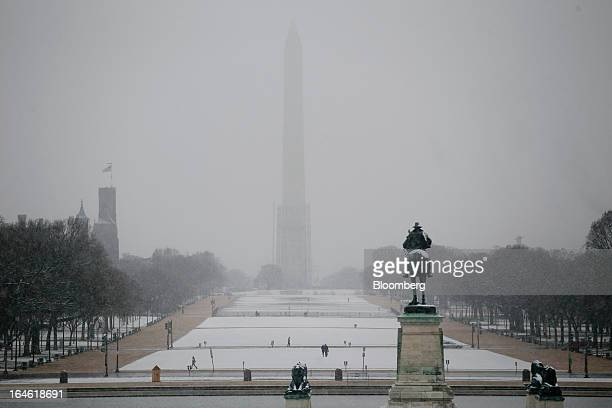 The Washington Monument is seen past snow covering the National Mall in Washington DC US on Monday March 25 2013 An early spring snowstorm tied up...
