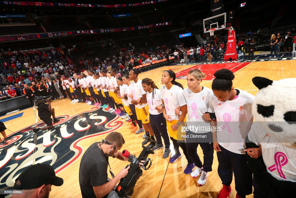 The Washington Mystics and the Los Angeles Sparks lock arms during the national anthem on August 16, 2017 at the Verizon Center in Washington, DC.