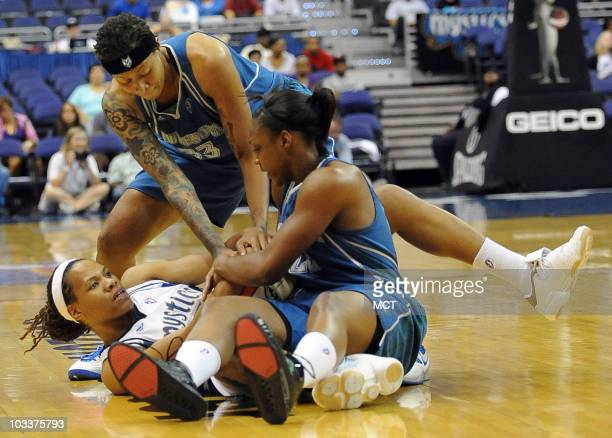 The Washington Mystics' Monique Currie, left, ties up the ball with the Minnesota Lynx's Monica Wright, right, and Seimone Agustus , after a scramble...