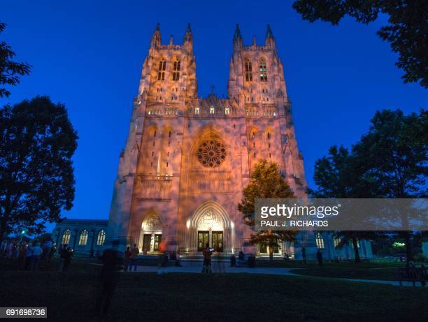 The Washington National Cathedral is lit up by orange lights as the bourdon bell tolls 93 times in honor of the average number of American killed by...