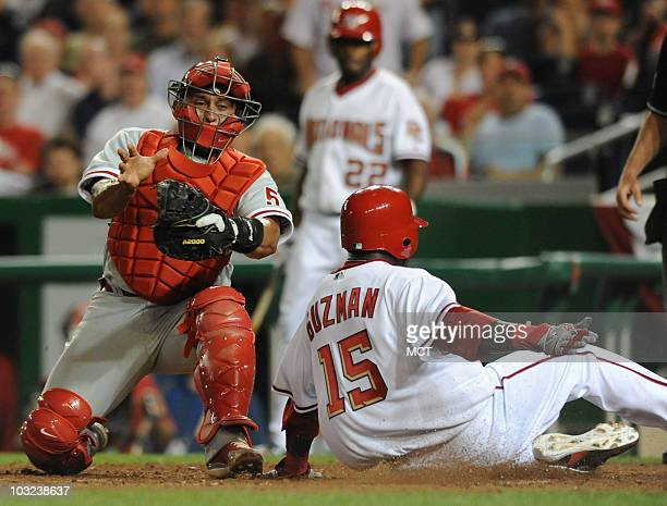 The Washington Nationals' Cristian Guzman avoids a tag by Philadelphia Phillies catcher Carlos Ruiz, left, on a sacrifice fly scoring attempt in the...