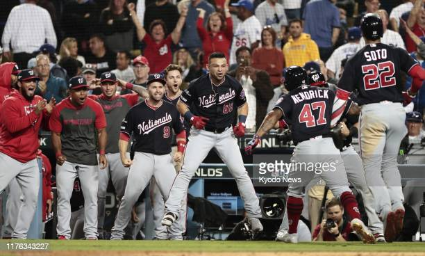 The Washington Nationals' Howie Kendrick is congratulated by teammates after hitting a grand slam against the Los Angeles Dodgers in the 10th inning...