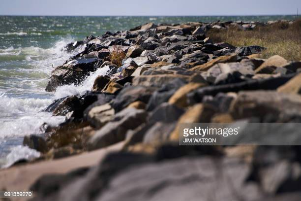 The water of the Chesapeake Bay crashes against the man-made sea wall that was engineered by the Army Corps of Engineers in 1999 to prevent erosion...