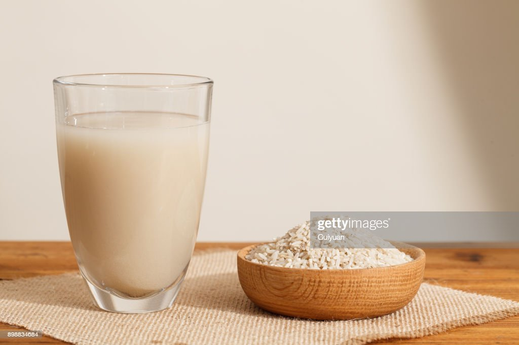 The water that clean out rice like milk in the glass,and Some rough rice in wooden bowl : Stock Photo