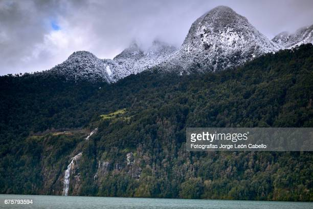 the waterfall of the lake view with clouds and snow over de mountain during the winter andean lake crossing - azul turquesa stockfoto's en -beelden