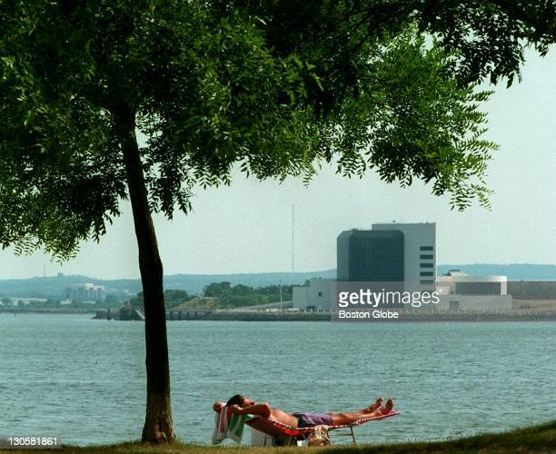 The waters off Southie provide a little relief for a sunbather on a sweltering afternoon with another waterfront icon of the city the John F Kennedy...