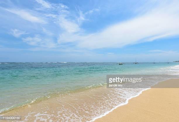 the waves impacted a row of white bubbles left on the golden beach. - riva dell'acqua foto e immagini stock