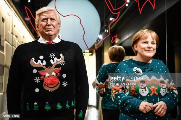 The wax figures of US President Donald Trump and German Chancellor Angela Merkel are pictured in Christmasthemed sweaters at the Grevin Wax Museum on...